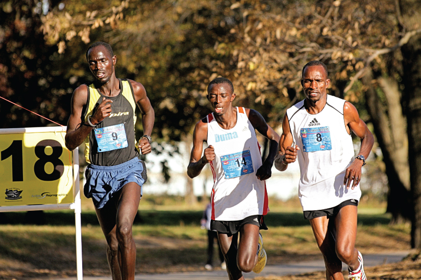 This photo shows three young men running in a competitive marathon.