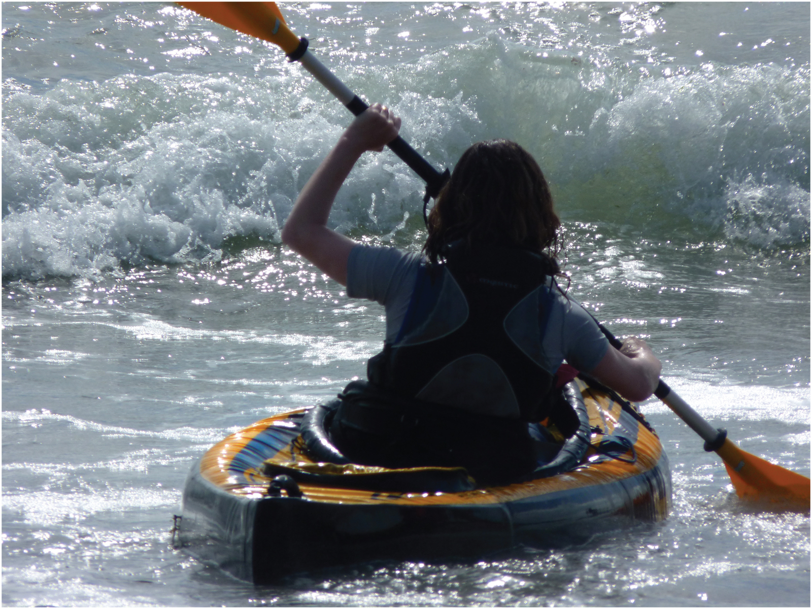 This picture shows a girl kayaking in the ocean.