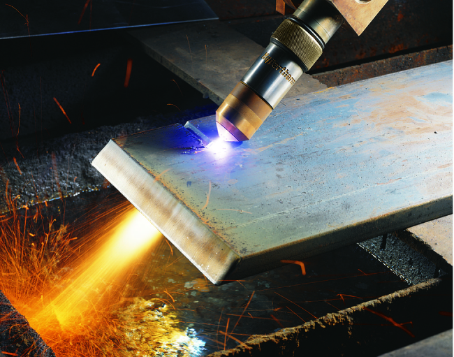 A cutting torch is being used to cut a piece of metal. Bright, white colored plasma can be seen near the tip of the torch, where it is contacting the metal.
