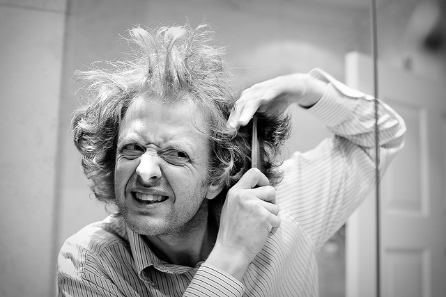 A man trying to tame his crazy hair