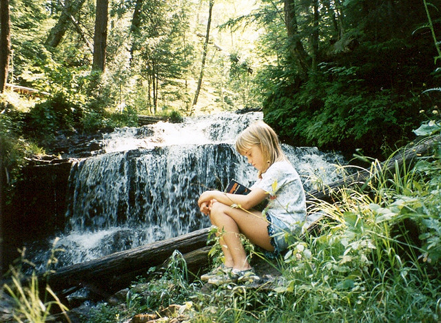 A young girl reading a book on a rock near a peaceful waterfall