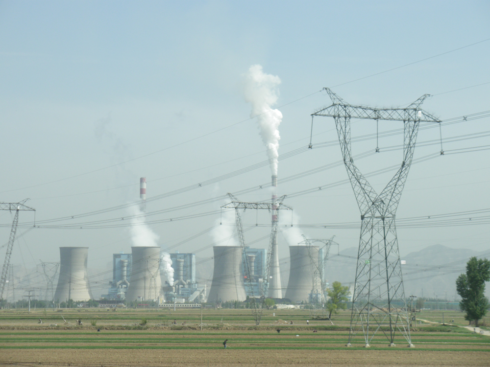 A distant view of a coal-fired power plant with clearly visible cooling towers generating electric power and emitting a large amount of gases.