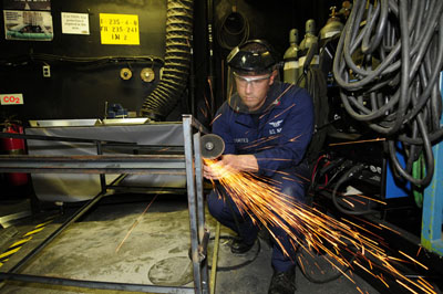 The figure shows a mechanic cutting metal with a metal grinder. The sparks are emerging from the point of contact and jumping off tangentially from the cutter.