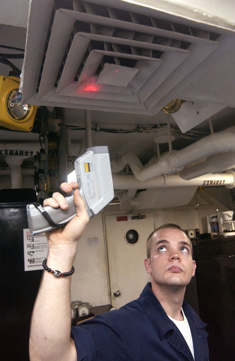 A man holds a device that looks like a gun or a check-out scanner up toward an air vent. A red light emanates from the device and shines on the vent.
