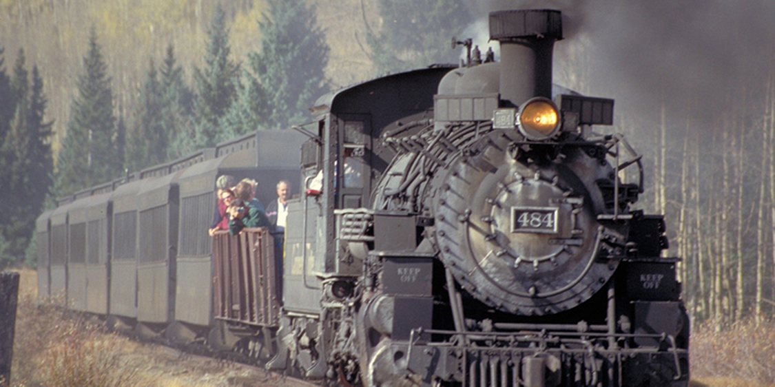 A steam engine and several passenger cars are shown traveling down a train track. The train has some people on board.