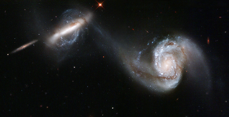 Two spiral galaxies show the strong gravitational attraction between them as their arms appear to reach out toward one another.
