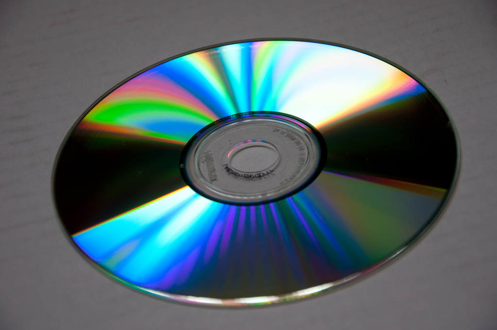 Photograph of the reflective side of a C D. Regions of the disc reflect a rainbow of colors.