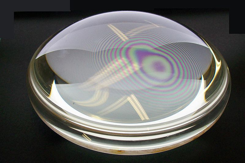 This figure shows rainbow-colored concentric rings obtained when two plano-convex lenses are placed together with their flat surfaces in contact.
