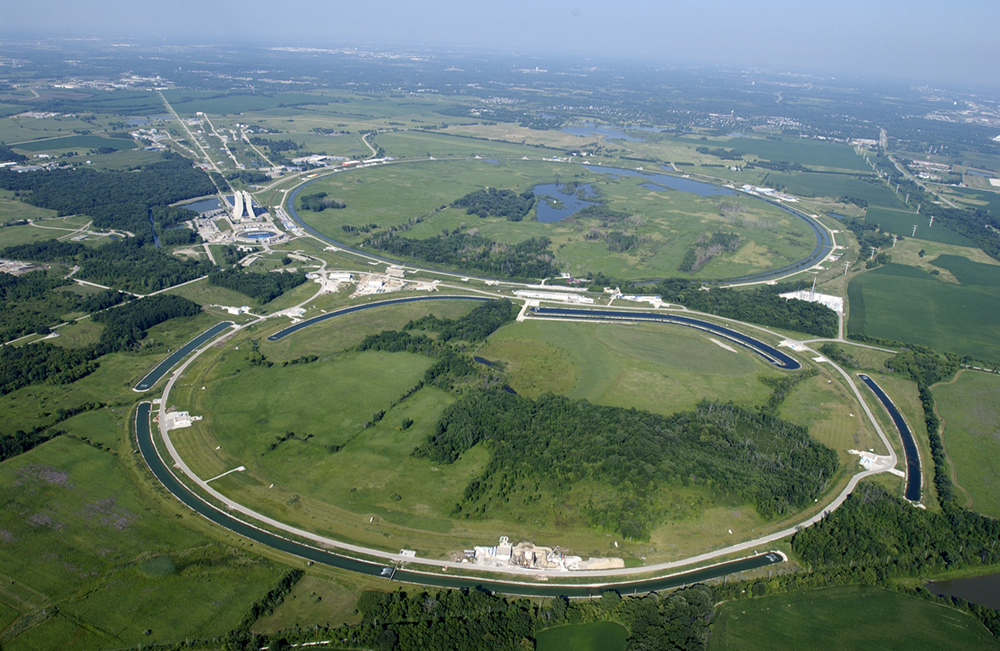 An aerial view of the Fermi National Accelerator Laboratory. The accelerator has two large, ring shaped structures. There are circular ponds near the rings.