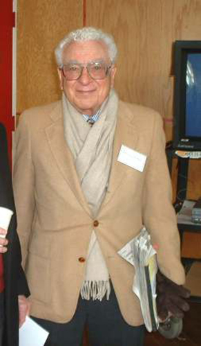 The image shows a picture of physicist Murray Gell Mann, who looks like a pleasant white-haired gentleman.