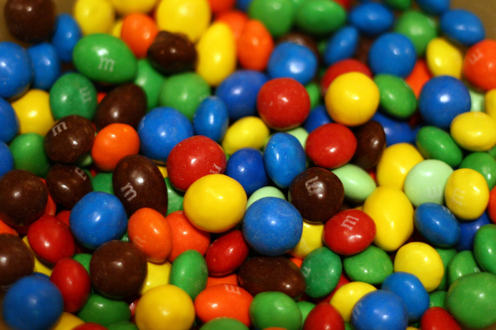 This is a photo of M&Ms piled together. The M&Ms are red, blue, green, yellow, orange and brown.