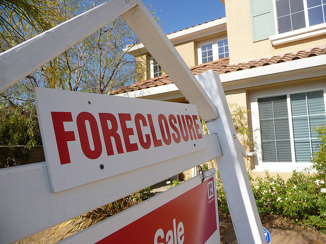 A foreclosure sign in front of a house