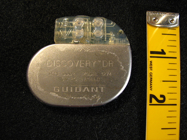 Pacemaker next to a ruler, showing that it is no bigger than two inches