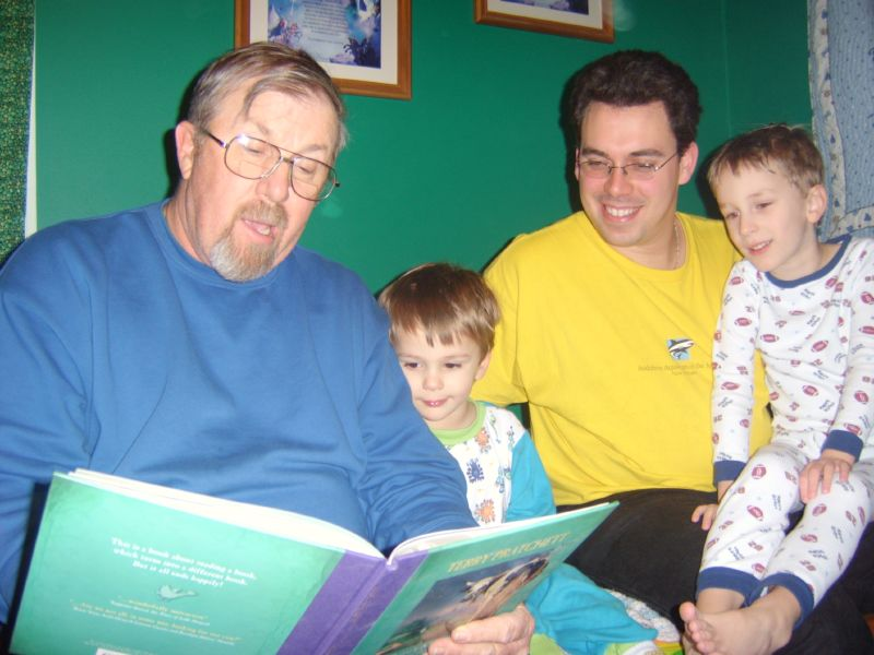 Grandpa reading to 2 kids and an adult