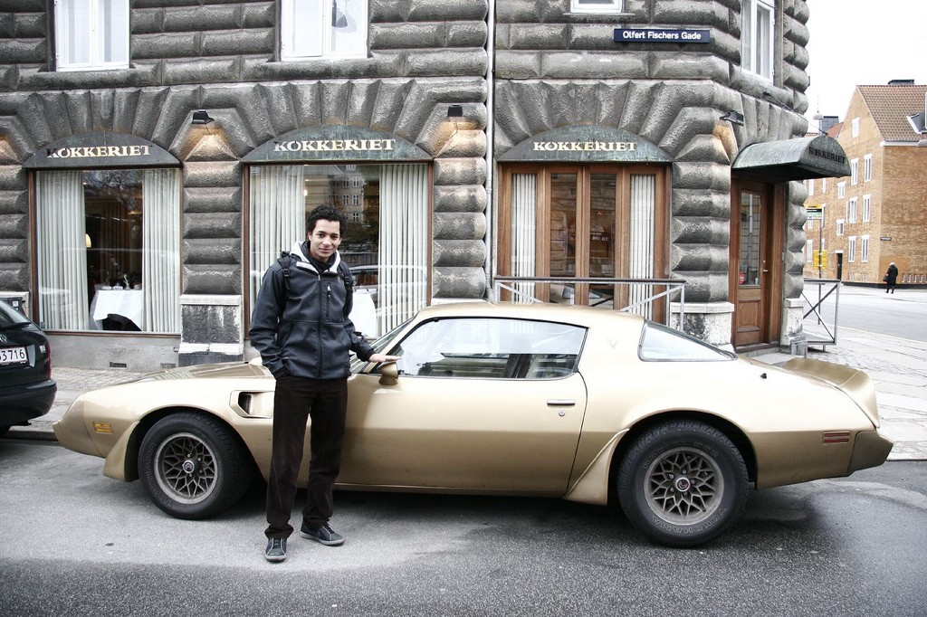 A young man standing next to an old sports car