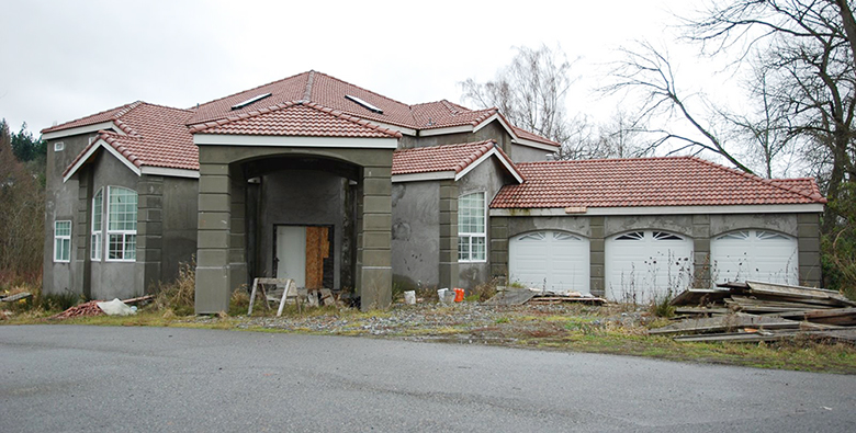 An image of a new home construction that appears to have most of the exterior completed but which clearly is not finished and has been abandoned for some time.