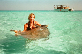 A photograph shows a woman standing in the ocean holding a stingray.