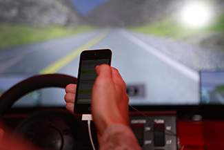 A person's right hand is holding a cellular phone. The person is in the driver's seat of an automobile while on the road.