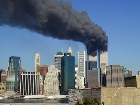 A photograph shows the World Trade Center buildings, shortly after two planes were flown into them on the morning of September 11, 2001.  Thick, black clouds of smoke stream from both buildings.