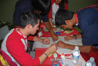 A picture shows four people gathered around a table attempting to figure out a problem together.