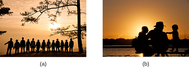Photograph A shows a large group of people holding hands with the sun setting in the distance. Photograph B shows a close relationship between three people by the water.