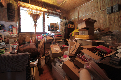A photograph shows a small room containing tall piles of boxes, overflowing with papers, binders, and various other possessions. Much of the furniture and floor are concealed beneath these other objects.