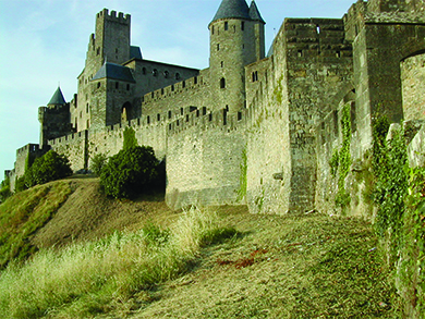 A photograph shows the medieval walled city of Carcassonne. It is surrounded by a high double wall with slots at the top, likely for archers or other defenders to use, and it incorporates several round parapets with narrow window openings.