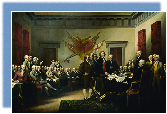 A painting shows members of the committee that drafted the Declaration of Independence presenting their work to the Continental Congress. Five men, including John Adams, Thomas Jefferson, and Benjamin Franklin, stand in front of a table at which other men are seated or standing. Jefferson is placing papers on the table. The room is filled with seated men, apparently the rest of the Continental Congress. British flags are mounted on the wall behind them.