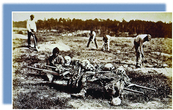 A photograph shows several African American men collecting the bones from a battleground in Virginia. In the foreground, one man prepares to carry away a pile of skulls and body parts.