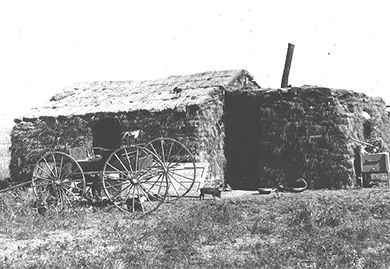 A photograph shows a sod house with a wagon in front of it.