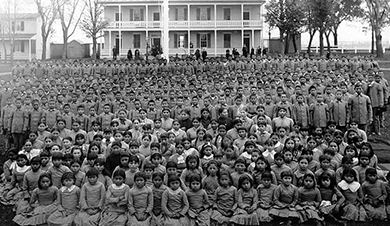 A photograph shows a large, posed group of Native American children at an Indian school. The girls sit in the front in collared dresses. The boys stand at the back in button-down shirts and slacks.