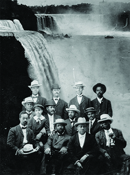 A photograph shows ten posed men, one of whom sits with a little boy. W. E. B. Du Bois is seated in the center.