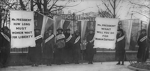 "A photograph shows Alice Paul and the Silent Sentinels picketing outside of the White House. Each woman wears a banner stating her alma mater. The women hold two large signs, the first of which reads ""Mr. President/How Long Must Women Wait For Liberty."" The second sign reads ""Mr. President/What Will You Do For Woman Suffrage."""