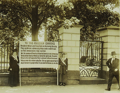 "A photograph shows two suffragists standing in front of the White House gate, holding a large sign between them. The text of the sign reads as follows: ""President Wilson and Envoy Root are deceiving Russia. They say 'We are a democracy. Help us win a world war so that democracies may survive.' We, the women of America tell you that America is not a democracy. Twenty million American Women are denied the right to vote. President Wilson is the chief opponent of their national enfranchisement. Help us make this nation really free. Tell our government that it must liberate its people before it can claim Russia as an ally."""