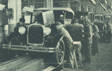 A photograph shows assembly line workers producing Ford automobiles.