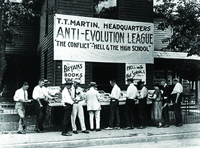 "A photograph shows a group of men reading literature that is displayed outside of a building. The building bears a large sign reading ""T. T. Martin, Headquarters / Anti-Evolution League / 'The Conflict'-'Hell and the High School.'"""