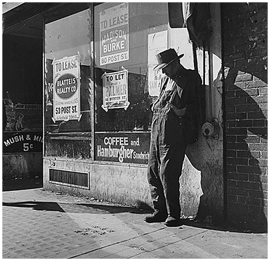 "A photograph shows an elderly destitute man leaning against a vacant storefront in San Francisco, California. The window is covered with signs indicating various properties that are ""to lease."""