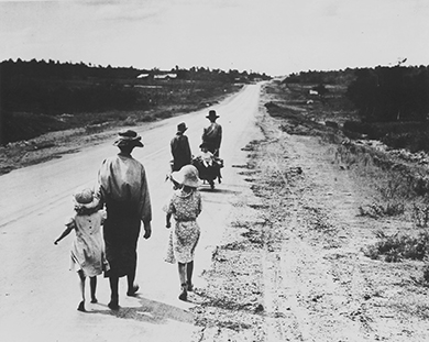 A photograph shows six Dust Bowl refugees—three adults, two children, and a baby—walking down a road. The baby rides in a small wagon.