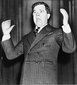 A photograph depicts Huey Long speaking and gesturing with his hands.