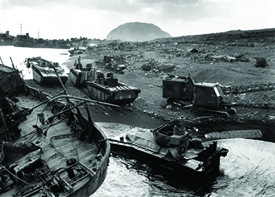 A photograph shows American forces arriving ashore on the dark sands of Iwo Jima. Mount Suribachi is visible in the background.