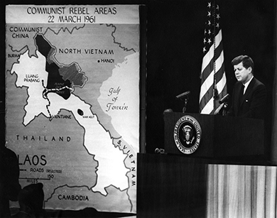 """A photograph shows President Kennedy standing at a podium delivering a speech. Beside him hangs a large map of Southeast Asia, labeled """"Communist Rebel Areas/22 March 1961."""""""