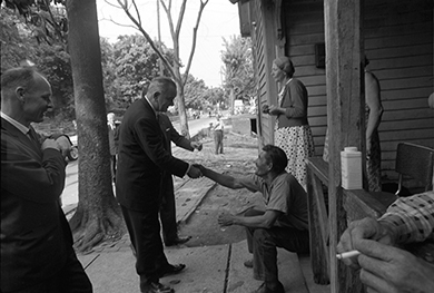 A photograph shows President Johnson standing on a street outside of a house, several of whose inhabitants sit and stand on the porch. He shakes the hand of a seated man while two other officials look on.