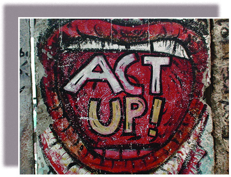 """A panel of graffiti on the Berlin Wall shows a wide-open mouth, within which are the words """"ACT UP!"""""""
