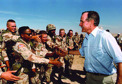 A photograph shows George H. W. Bush greeting and shaking hands with U.S. troops stationed in Saudi Arabia.