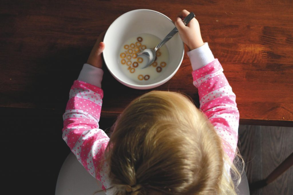 Child with a bowl of cereal and milk